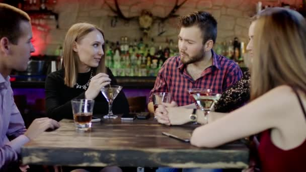 Společnost mladých lidí je chatování a usmíval se v baru
