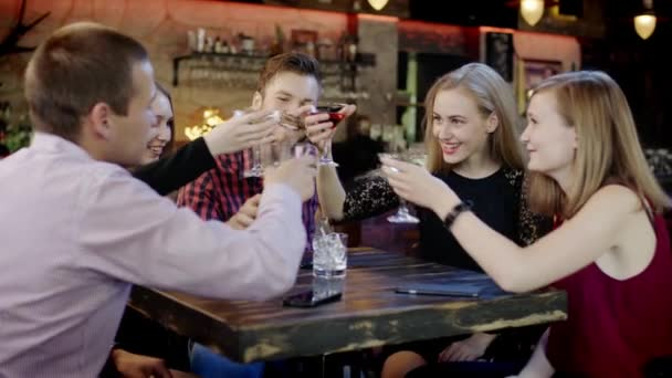company of young friends is clinking glasses in the bar