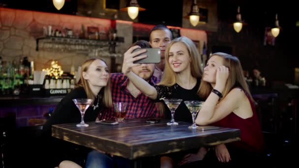 company of young people is taking selfie in the bar