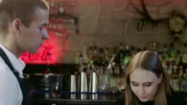 Boldog fiatal ember ül a bár menü kártya olvasó és parancsokat adni a férfi pincér