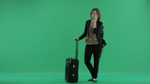 Touristin mit Koffer telefoniert