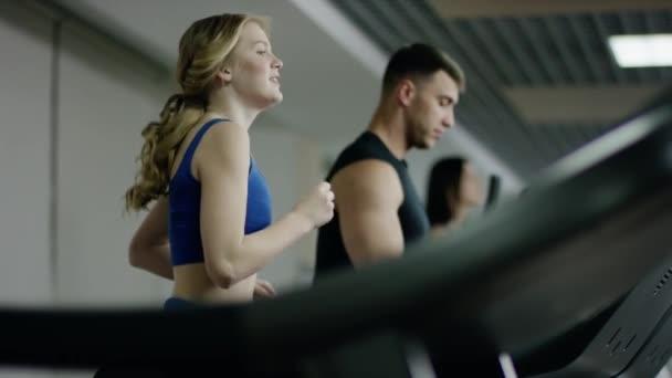 hübsche lächelnde blonde Frau läuft auf Laufband