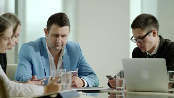 people using phones on meeting