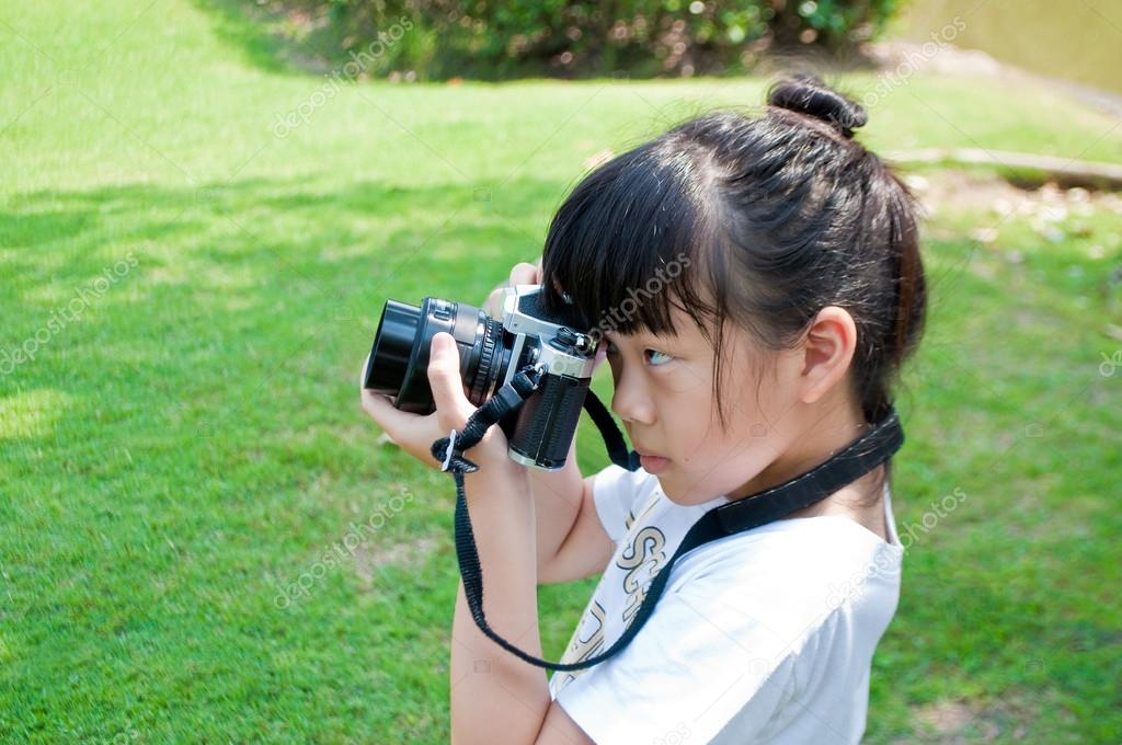Девочка фотографируется на улице.