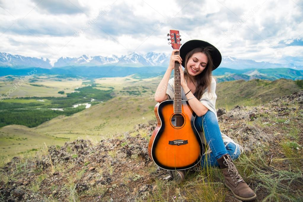 girl in a hat with a guitar sitting on the grass on a background
