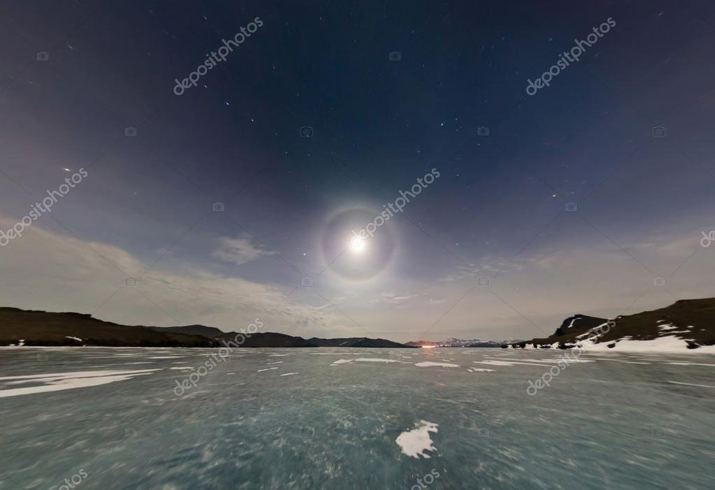 Moon halo in the night sky over Lake Baikal ice. Stereographic p