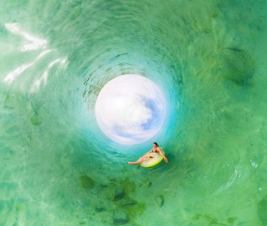 Girl in inflatable ring floating in the azure sea