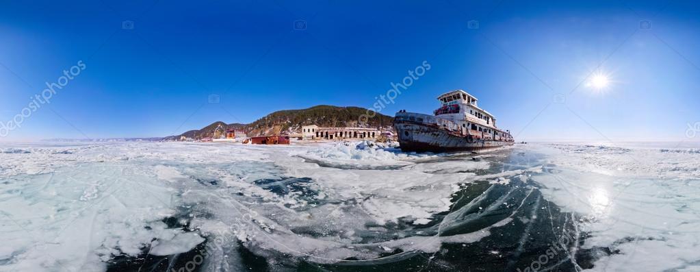 Old rusty ship on the coast of Lake Baikal among ice. Panorama 3