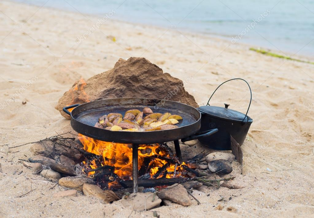 Fried potatoes on a homemade iron pan on the beach