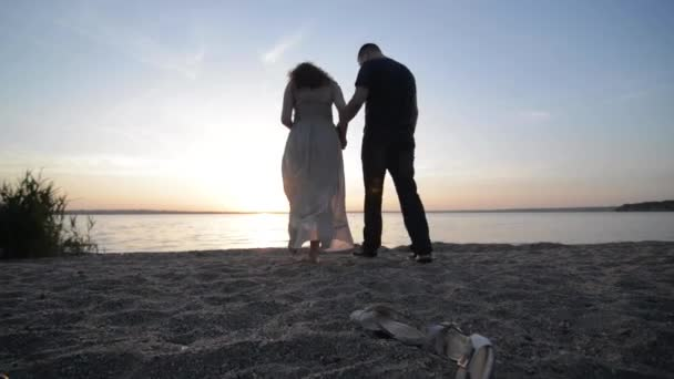 Couple expexting baby walking on a river shore holding hands on sunset