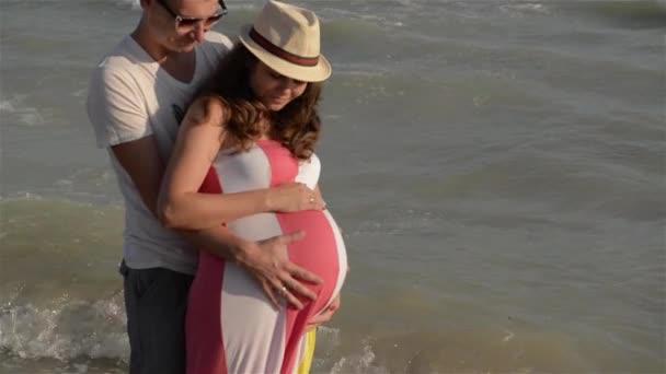 Pár expexting dítě na pobřeží moře hospodářství ruce na slunce pozadí