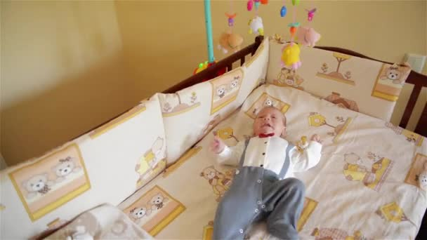 Little cute baby boy lying in crib with toy, boy crying