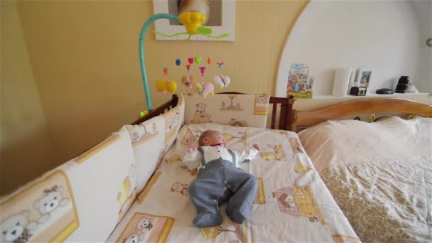 Little cute baby boy lying in crib with toy