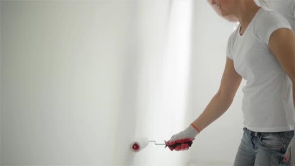 junges Paar dekoriert seine neue Wohnung. Sie streichen die Wand