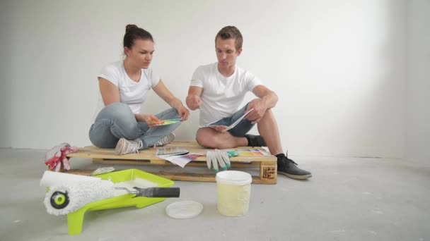 Young couple moving in a new home. Wife and husband selecting a color for a wall