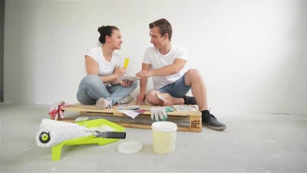 Mladý pár, pohybující se v novém domově. Manželka a manžel výběr barvy na zeď