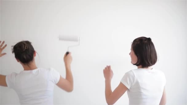 Two girls singing in the paint roller, friends are doing repairs and dancing