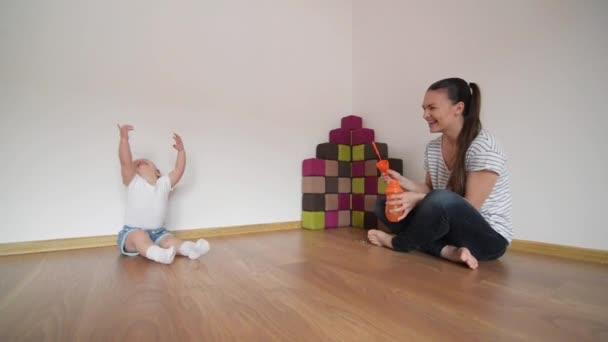 Mladá matka foukání bublin pro svou dceru, dívka, směje se a baví