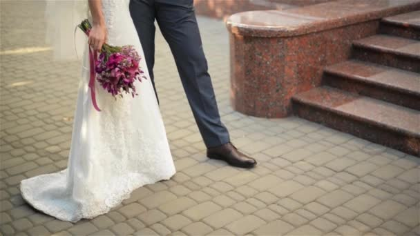 feet of bride and groom walking, wedding shoes, bridal bouquet