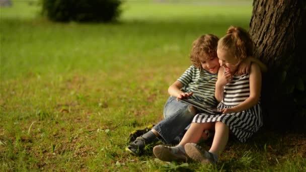 Zwei süße Kinder mit digitalem Tablet im Sommergarten