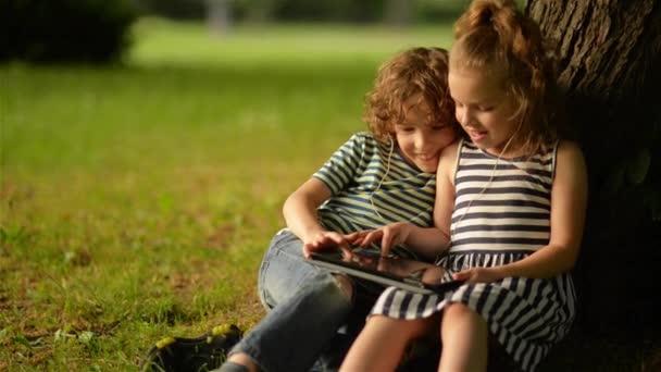 two cute kids using digital tablet in summer garden