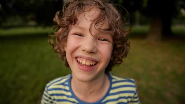 Cute boy laughing in the park, close-up, slow motion