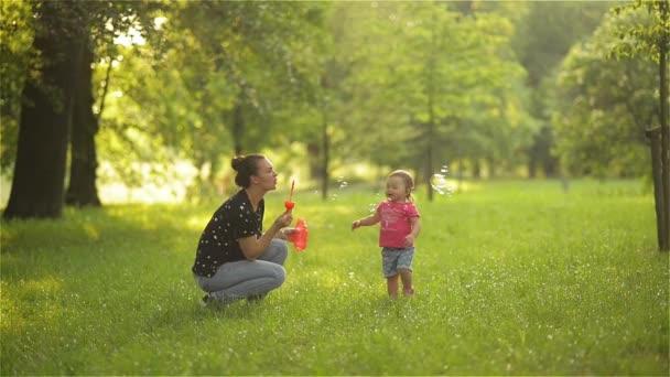 Matka a dívka foukání mýdlové bubliny venkovní. Rodič a dítě baví v parku.