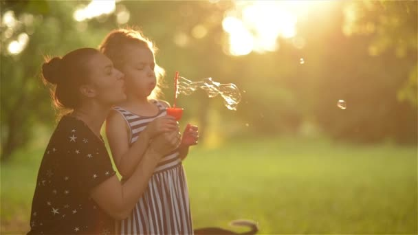 Krásná matka s dcerou v přírodě, takže mýdlové bubliny a směje se