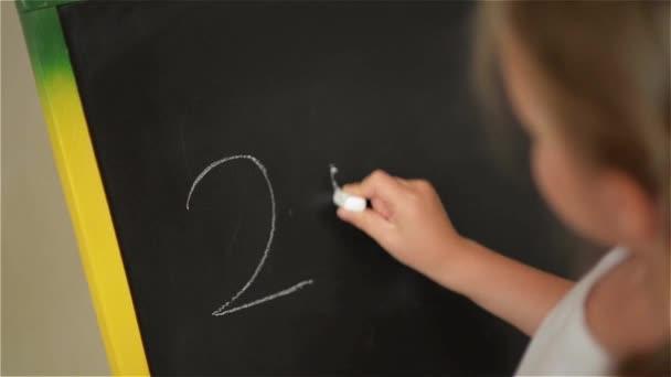 Školák cvičit jednoduché matematické na tabuli křídou