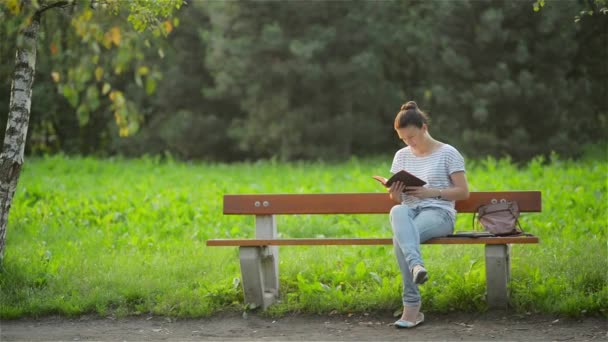 Beautiful Woman Sitting On A Bench In The Park And Reading A Book