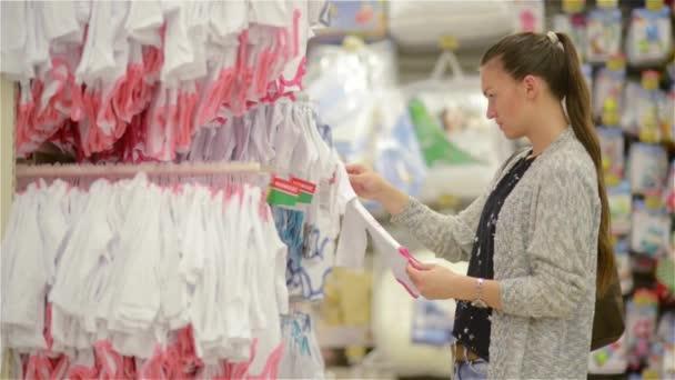 09b97703b27 Atractivo joven madre comprar ropa para niños en una tienda de ropa por  menor ver los artículos en una parrilla, hermosa mujer elige ropa de bebé en  la ...