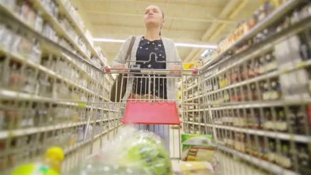 Donna caucasica camminando lungo scaffali commercio allingrosso e prendendo la merce nel carrello del negozio, bella moglie giovane lo shopping in un supermercato