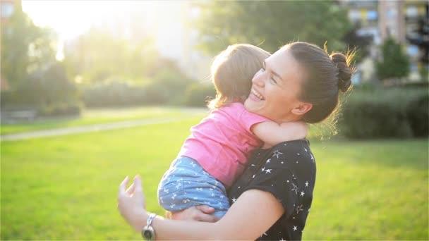 Matka a dítě jsou objímání a venkovní v přírodě, rodina vesele baví. Matka a dítě líbání, směje se a objímání
