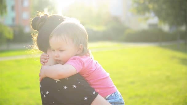 Mother and child are hugging and having fun outdoor in nature, mother hugs her little cute daughter