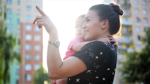Šťastná matka a dcera tráví společně čas venku, ukazují prstem a nadšeně vzhlédl, s radostí trávit čas v přírodě
