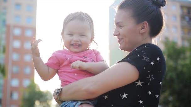 Krásná příroda matka a dcera. Krásná maminka a její dítě spolu hrají v parku. Maminka a děťátko směje venku