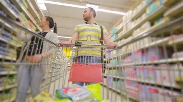 Těší, nákupy společně. Lepení šťastný mladý pár navzájem a usmíval se při chůzi při chůzi v obchod s potravinami s nákupní košík