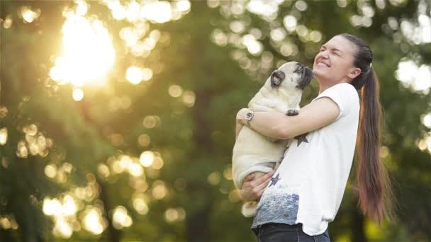 Žena šťastná s dlouhými tmavými vlasy drží malé krásný mladý pes v zahradě, dívka si hraje s její Mopy v parku