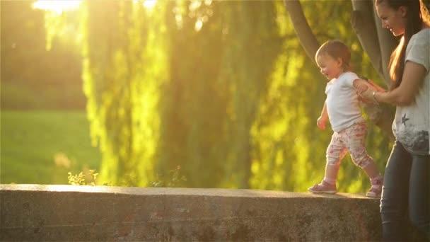Anya és lánya, séta a természetben, gyönyörű anya ő kis gyerekekkel fut a parkban, egy meleg nyári napon