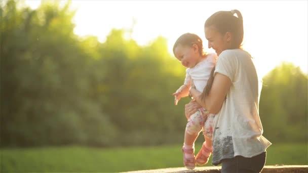 Rodina tráví čas v přírodě. Mami, něžně objímat dcera, krásná maminka hrát se svými dětmi v parku