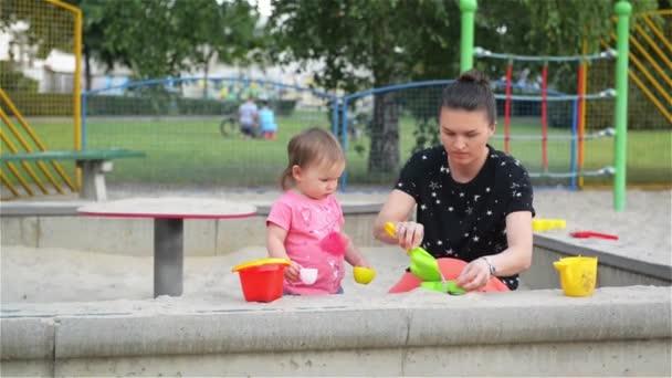 Matka a dítě dcera hraje a tvarů v karanténě, krásná mladá maminka tráví čas se svými dětmi venku