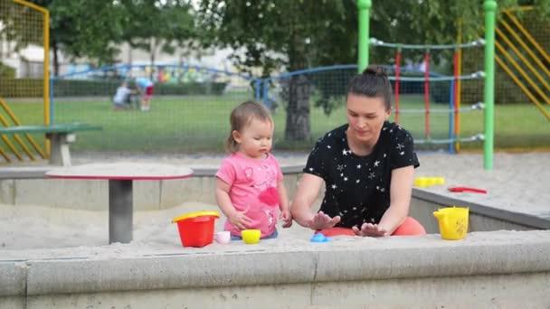Mutter und kleine Tochter spielen und formen im Sandkasten, schöne junge Mutter verbringt Zeit mit ihren Kindern im Freien