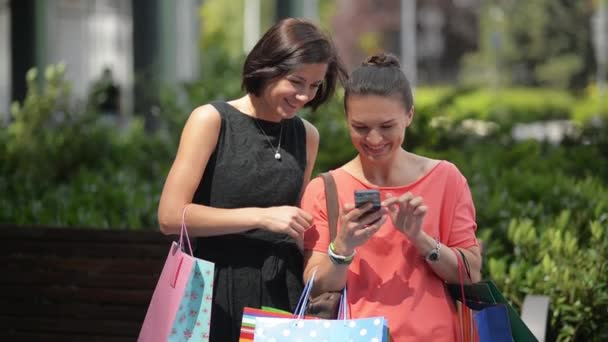 Two fashion girls with bags shopping with a smart phone in the street, beautiful woman using telephone