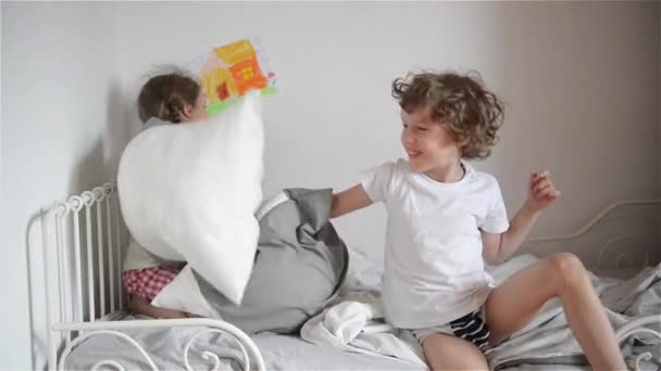 The brother and the sister have arranged fight by pillows on a bed in a bedroom.