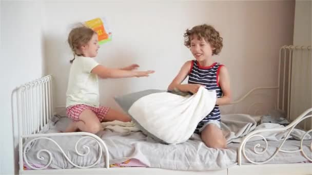 The brother and the sister have arranged fight by pillows on a bed in a bedroom. The naughty little girl beats the brother a pillow.