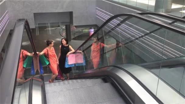 Dvě dívky pohybující se nahoru na eskalátoru v shopping mall, přátelé jsou nákupní v úložišti