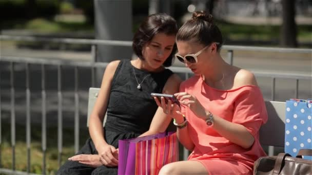 Young beautiful girls using smartphone sitting at the bus stop of city, Two friends female laughing on the bench