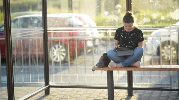 Young charming Caucasian female with trendy look use tablet while waiting transport on bus stop, woman sitting on a station against sunset background