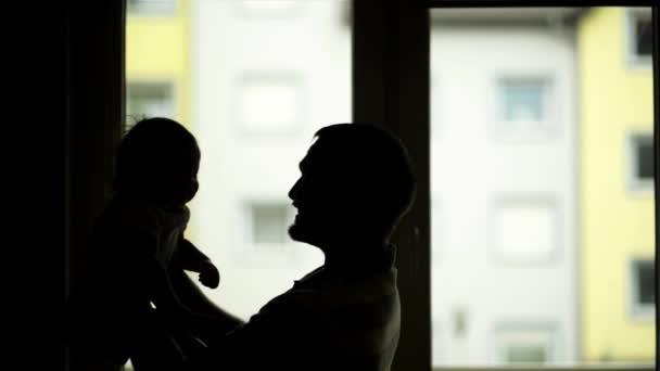 Siluety otce a dceru při západu slunce, otec hrál s jeho dítětem