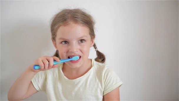 Aranyos kis lány pigtails szorgalmasan ecset fogai. A lány keze van a blue tooth ecset. Vidám kislány, keresi a kamerába